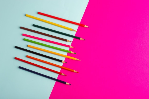 Vue de dessus crayons colorés bordés de bleu et rose bureau couleur dessin peinture art