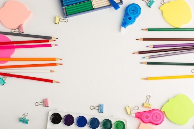 Vue de dessus crayons colorés avec des peintures et des autocollants sur la peinture de couleur de dessin d'art de bureau blanc