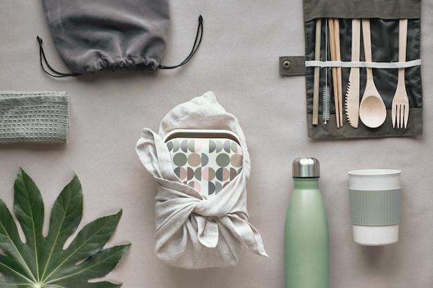 Vue de dessus créative, kit de déjeuner emballé sans déchets, boîte à lunch à emporter sur un sac en coton, organisateur de couverts en bambou, boîte à lunch en bambou et tasse réutilisable. mode de vie durable, mise en page à plat sur papier kraft.
