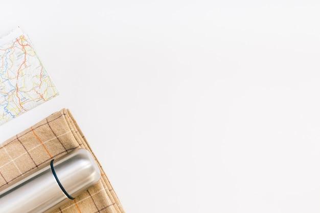 Vue de dessus créative à plat composition de voyage en plein air. couverture de carte thermos espace copie fond blanc.