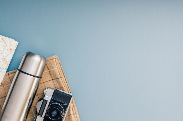 Vue de dessus créative à plat composition de voyage en plein air. couverture de couverts appareil photo rétro carte thermos fond bleu gris copie espace.