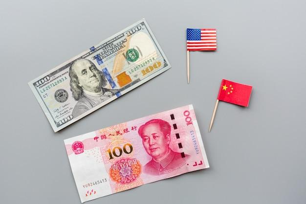 Vue de dessus créative plat lay de drapeaux américains et chinois et dollar américain d'argent liquide