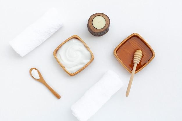 Vue de dessus de la crème au beurre pour le corps et miel sur fond blanc