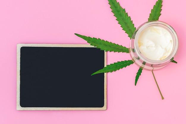 Vue de dessus de la crème de chanvre au cannabis avec une feuille de marijuana avec un tableau vide noir pour la maquette de texte