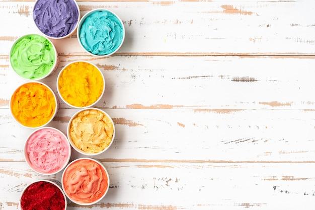Vue de dessus de la crème glacée arc en ciel coloré dans des tasses. espace de copie