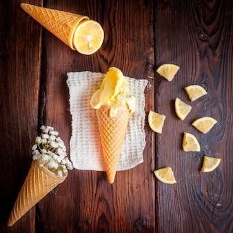 Vue de dessus de la crème glacée dans un cornet gaufré à l'orange et à la gypsophile dans des serviettes en chiffon