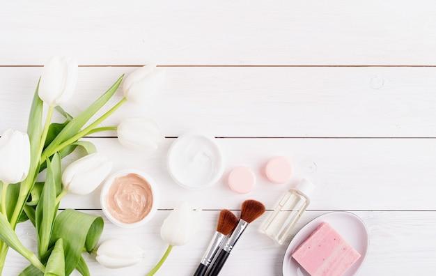 Vue de dessus des crèmes cosmétiques et du savon avec des tulipes blanches vue de dessus à plat sur fond en bois blanc