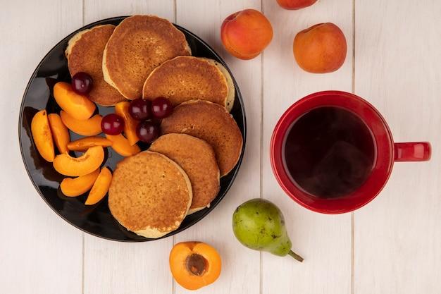 Vue de dessus des crêpes aux cerises et abricots en tranches dans la plaque et tasse de café aux poires et abricots sur fond de bois