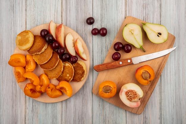 Vue de dessus des crêpes aux cerises et couper la pêche poire abricot avec un couteau sur des planches à découper sur fond de bois