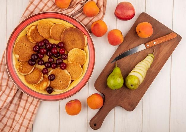 Vue de dessus des crêpes aux cerises dans une assiette sur un tissu à carreaux avec des poires entières et tranchées avec un couteau sur une planche à découper et des abricots sur fond de bois