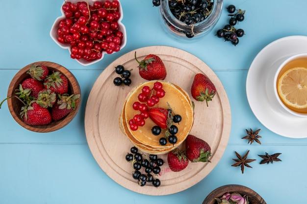 Vue de dessus des crêpes aux groseilles rouges et noires et fraises avec une tasse de thé sur une surface bleue