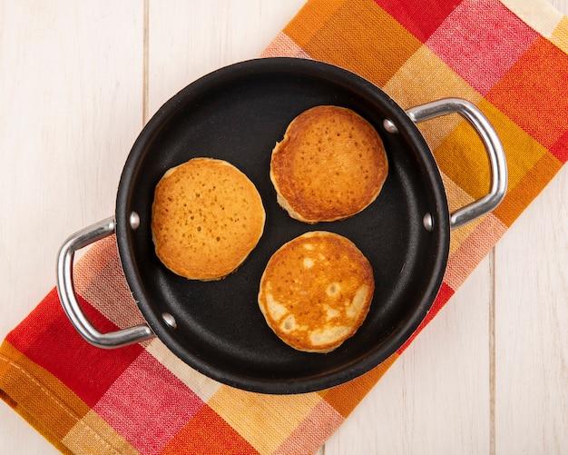 Vue de dessus des crêpes dans une casserole sur tissu à carreaux et fond en bois