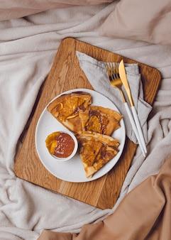 Vue de dessus des crêpes du petit déjeuner au lit avec de la confiture