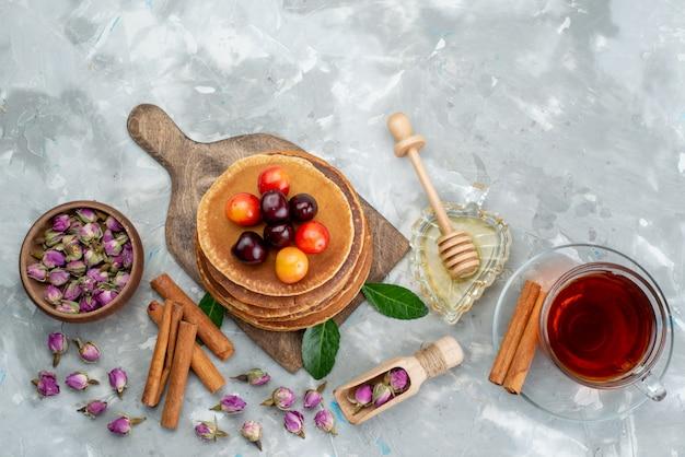 Une vue de dessus des crêpes rondes cuites au four et délicieuses avec des cerises et des fruits de gâteau à la cannelle