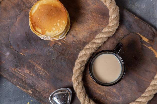Vue de dessus des crêpes rondes avec une tasse de lait noir sur le bureau en bois avec des cordes sur le fond gris repas petit déjeuner sucré