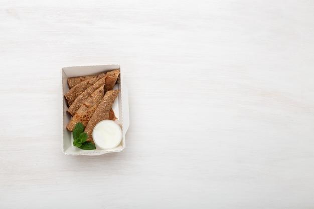 Vue de dessus des crêpes avec sauce à la crème sure dans une boîte à lunch blanche se trouvent sur un tableau blanc à côté des verts. concept de collation diététique, espace copie