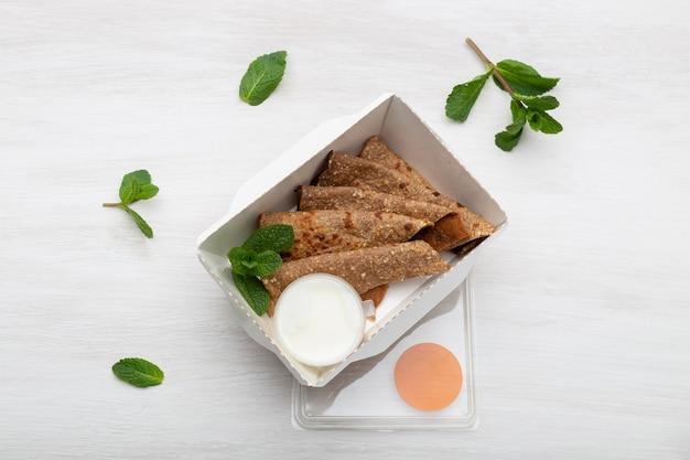 Vue de dessus des crêpes avec sauce à la crème sure dans une boîte à lunch blanche se trouvent sur un tableau blanc à côté des verts. concept de collation diététique.