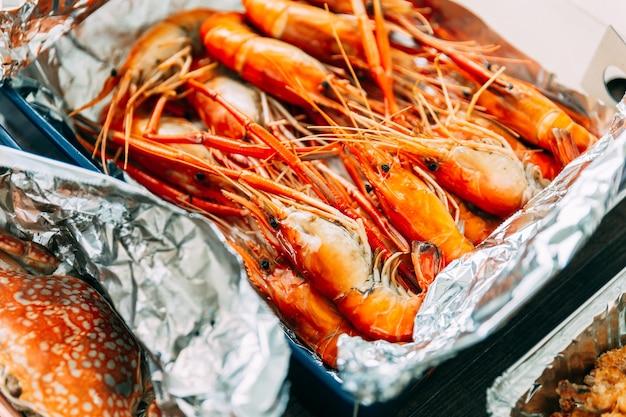 Vue de dessus de crevettes grillées thaïlandaises (crevettes) dans la coquille dans une boîte en papier.