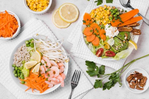 Vue de dessus de crevettes et de légumes sur des assiettes