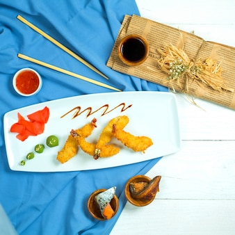 Vue de dessus des crevettes tempura servies avec du gingembre et du wasabi sur un plateau bleu et blanc