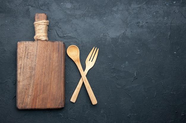 Vue de dessus croisé cuillère en bois et fourchette de service sur table sombre avec place de copie