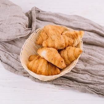Une vue de dessus de croissants cuits au four dans le panier en osier