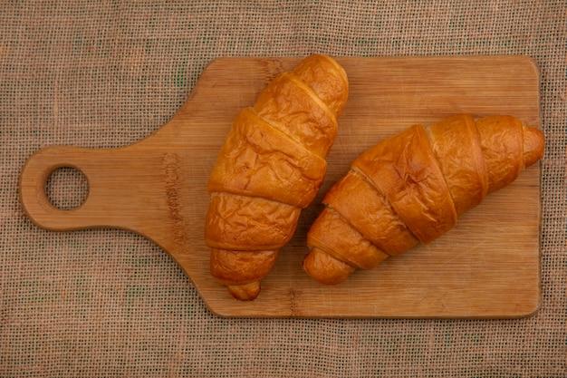Vue de dessus des croissants sur une planche à découper sur fond de sac