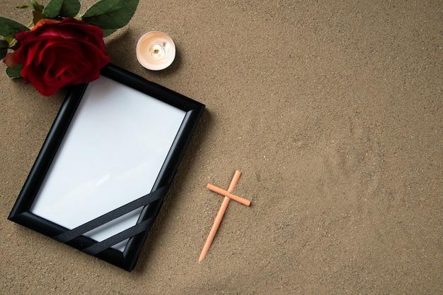 Vue de dessus de la croix de bâton avec fleur rouge et cadre photo sur le sable