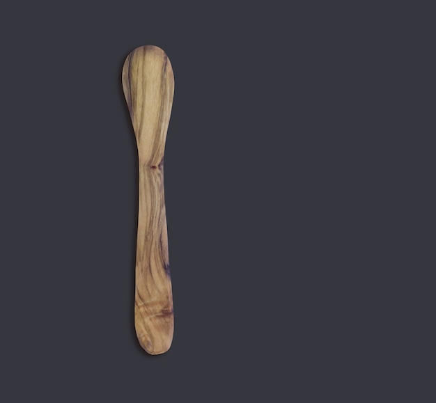 Vue de dessus d'une cuillère en bois d'olive isolée sur fond noir