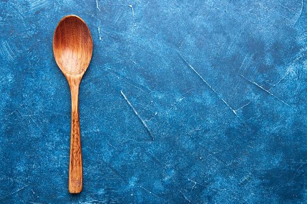 Vue de dessus cuillère en bois sur place libre de table bleue