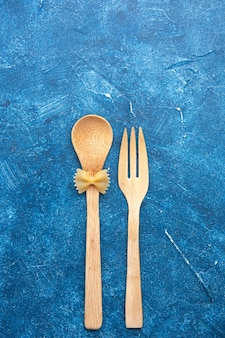 Vue de dessus cuillère fourchette en bois farfalle sur cuillère sur table bleue avec espace libre