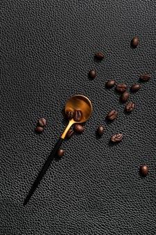 Vue de dessus de la cuillère d'or avec des grains de café