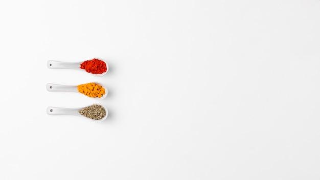Vue de dessus des cuillères blanches aux épices
