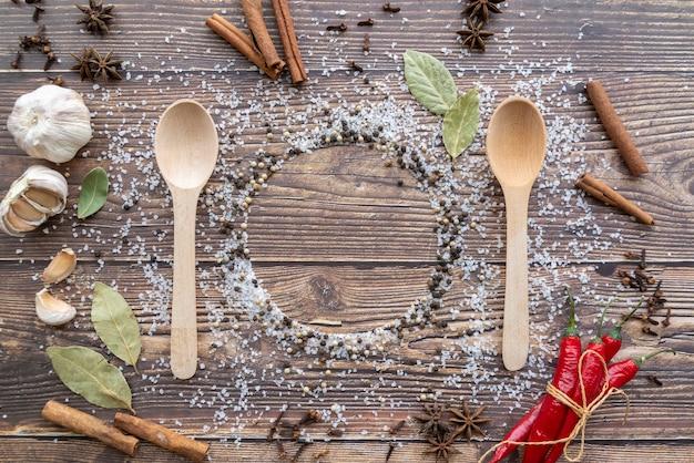 Vue de dessus des cuillères en bois avec condiments et bâtons de cannelle