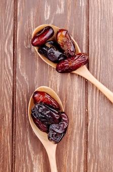 Vue de dessus des cuillères en bois avec des dates séchées sur fond de bois