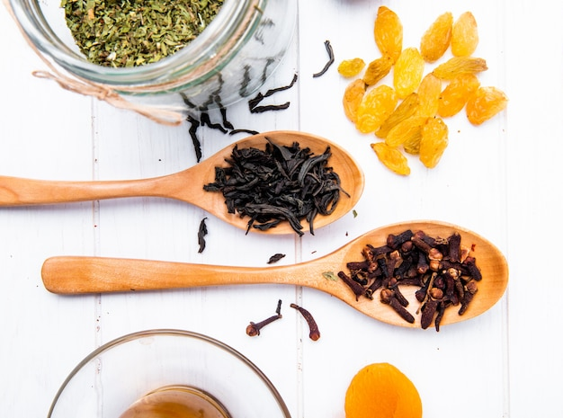 Vue de dessus des cuillères en bois avec des feuilles de thé noir sec et des épices de clou de girofle et des raisins secs épars sur bois blanc