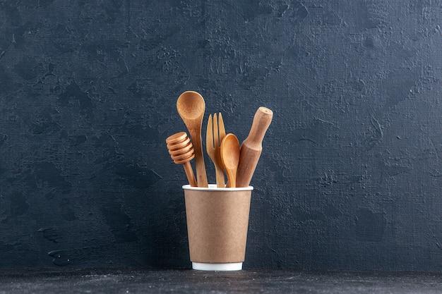 Vue de dessus des cuillères de cuisine en bois dans une cafetière en plastique sur un mur sombre