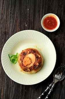 Vue de dessus de la cuisine indonésienne riz cuit à la vapeur au poulet (nasi tim ayam) avec œuf à la coque et poulet à la sauce soja sucrée