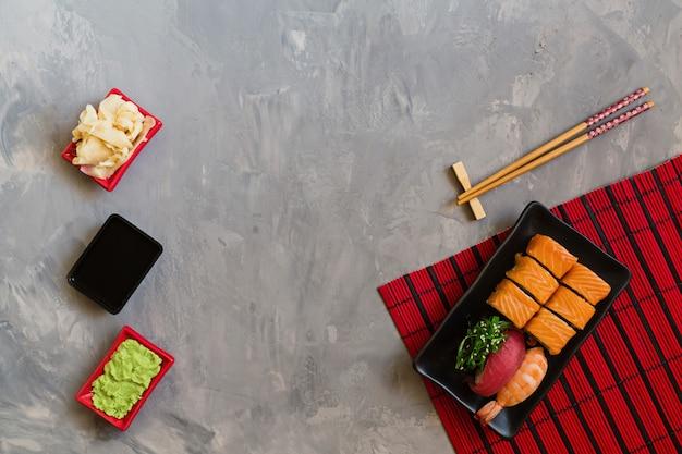 Vue de dessus sur la cuisine japonaise traditionnelle avec des sushis sur fond gris