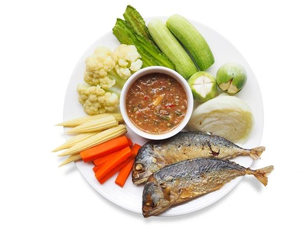 Vue de dessus de la cuisine thaïlandaise traditionnelle avec de la pâte de crevettes au chili ou nam prik kapi, du maquereau frit et des légumes bouillis sur une plaque blanche.