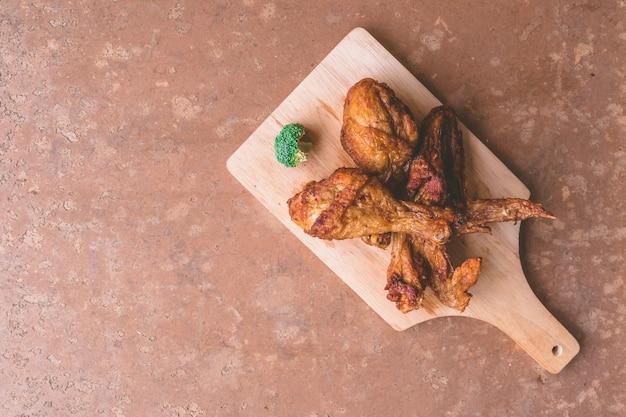 Vue de dessus des cuisses de poulet frites et des ailes sur un plateau en bois.