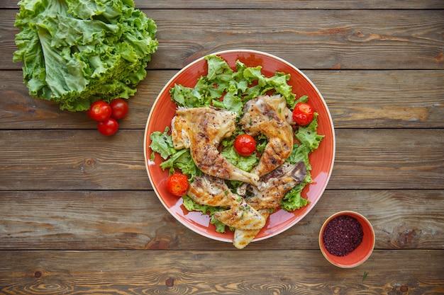 Vue de dessus de cuisses de poulet grillées servies sur des feuilles de laitue avec tomates cerises
