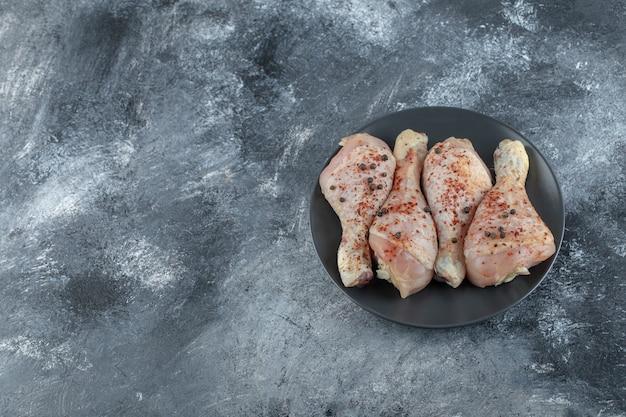Vue de dessus des cuisses de poulet marinées crues sur plaque noire sur fond gris.