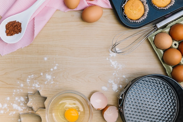 Une vue de dessus de cupcake fait maison et d'ingrédients sur un bureau en bois