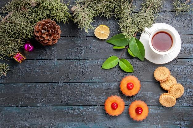 Vue de dessus cupcakes cerise cône branches de sapin tranche de citron une tasse de thé et biscuits sur un sol en bois foncé avec espace copie