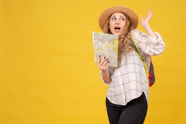 Vue de dessus de curieuse fille de voyage portant son chapeau et sac à dos tenant la carte sur jaune