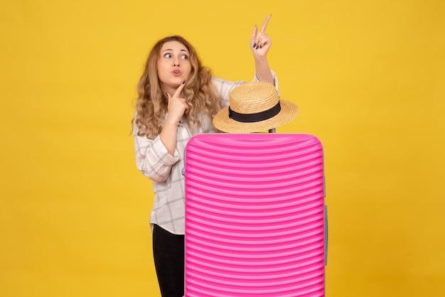 Vue de dessus de curieuse jeune femme debout derrière son sac rose