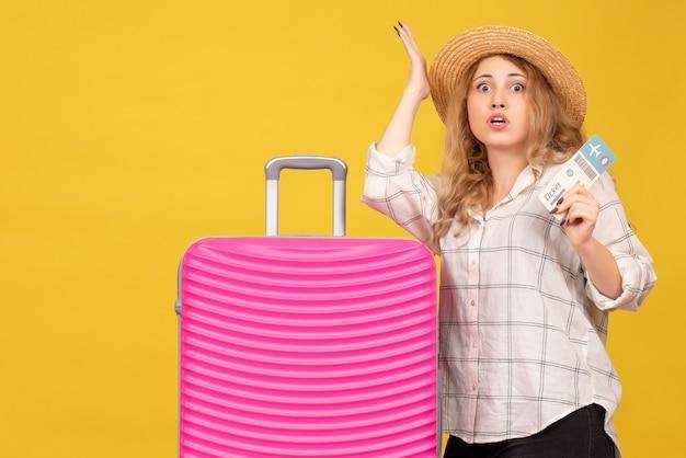 Vue de dessus de curieuse jeune femme portant un chapeau montrant un billet et debout près de son sac rose