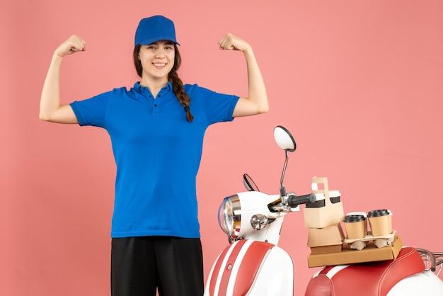 Vue de dessus d'une dame de messagerie confiante debout à côté d'une moto avec du café et des petits gâteaux dessus sur fond de couleur pêche pastel