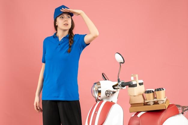 Vue de dessus d'une dame de messagerie debout à côté d'une moto avec du café et des petits gâteaux dessus regardant quelque chose avec soin sur fond de couleur pêche pastel